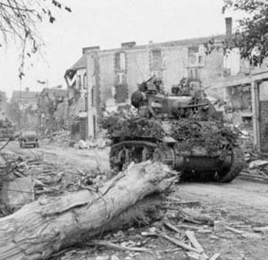 Light Tank M5 passes through the wrecked streets of Coutances in Normandy.