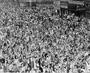 Crowd of people, many waving, in Times Square on V-J Day at time of announcement of the Japanese surrender in 1945 / World-Telegram photo by Dick DeMarsico. Date 14 August 1945