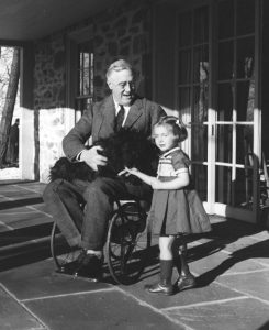 Franklin D. Roosevelt, Fala and Ruthie Bie at Hill Top Cottage in Hyde Park, N.Y. The better of two extant photos of FDR in a wheel chair. February 1941