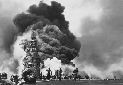 American aircraft carrier USS Bunker Hill burns after being hit by two kamikaze planes within 30 seconds.